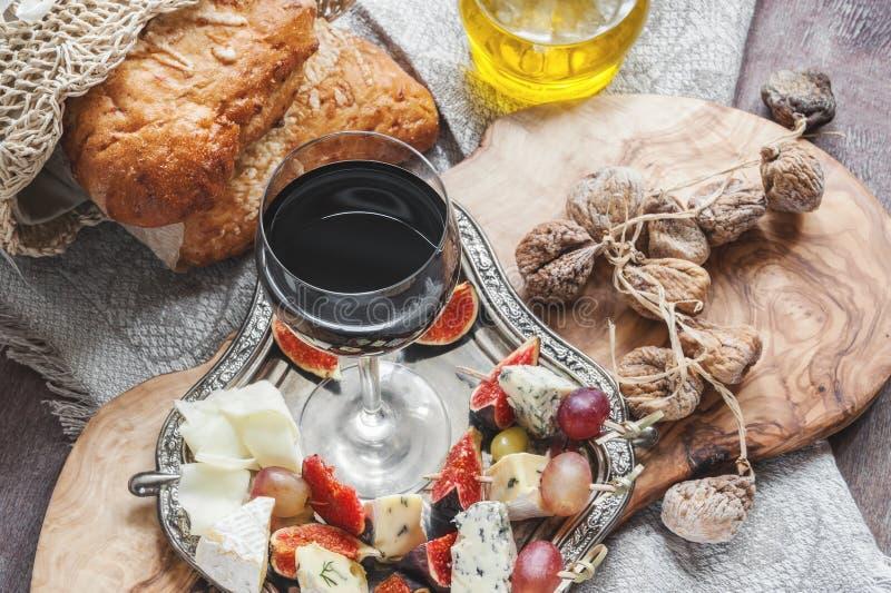 Ett exponeringsglas av torrt rött vin- och italienareFocaccia bröd med ost och olivolja och solen torkade tomater Selektivt fokus arkivbild
