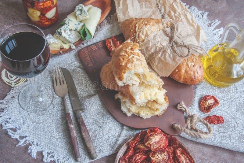 Ett exponeringsglas av torrt rött vin- och italienareFocaccia bröd med ost och olivolja och solen torkade tomater Selektivt fokus royaltyfri bild