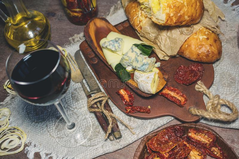 Ett exponeringsglas av torrt rött vin- och italienareFocaccia bröd med ost och ett ostuppläggningsfat med fikonträd och Gorgonzol royaltyfria foton