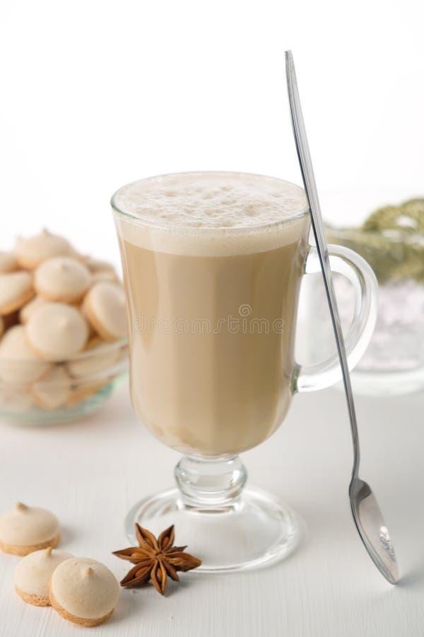 Ett exponeringsglas av varmt lattekaffe med söta kakor Symbolisk bild arkivbilder