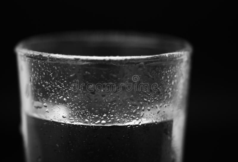 Ett exponeringsglas av vatten i studio med svart bakgrund fotografering för bildbyråer