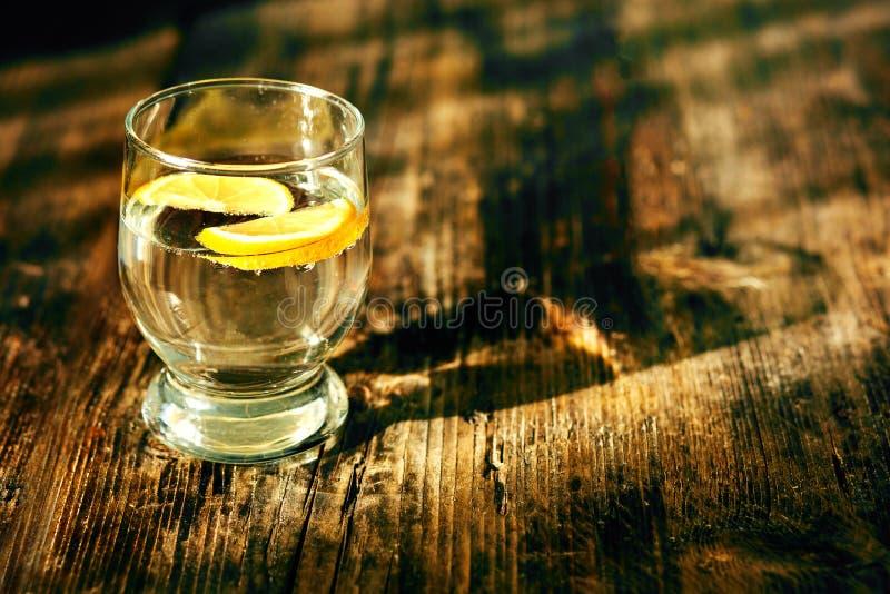 Ett exponeringsglas av vatten och en citron royaltyfria bilder