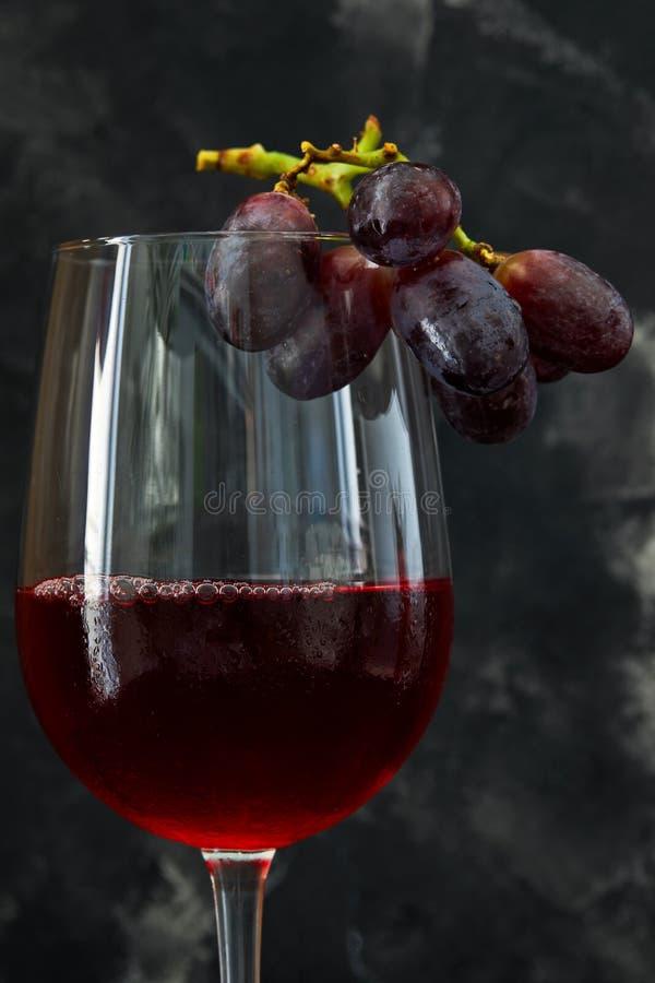 Ett exponeringsglas av vin med druvor på en mörk bakgrund fotografering för bildbyråer