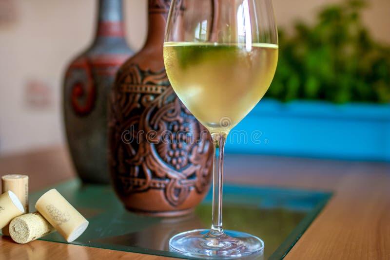 Ett exponeringsglas av vin och flaskor i perspektiv royaltyfria foton