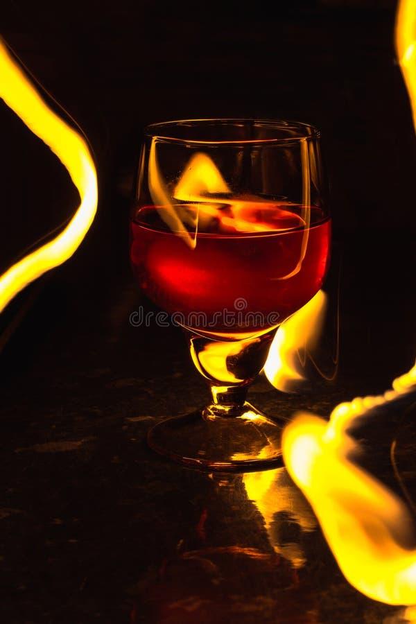 Ett exponeringsglas av vin på en svart bakgrund Partiklubbaunderhållning arkivbild