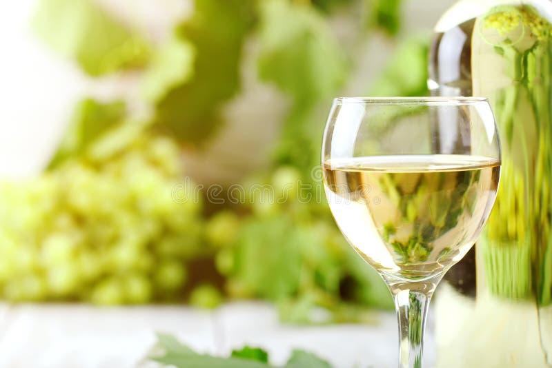 Ett exponeringsglas av vitt vin, nya druvor och en flaska av vitt vin på en trätabell royaltyfria foton