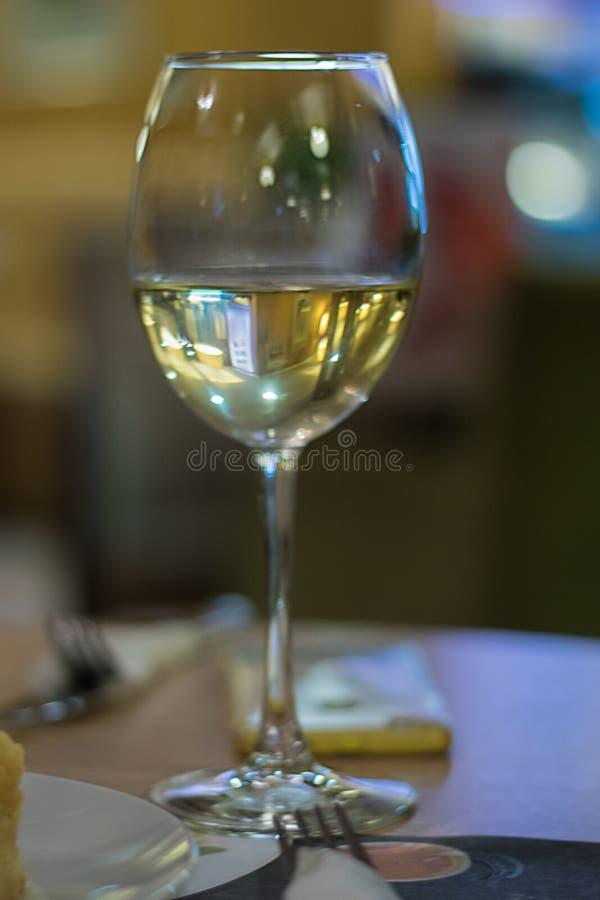 Ett exponeringsglas av vitt vin på defocudesbakgrund royaltyfri foto