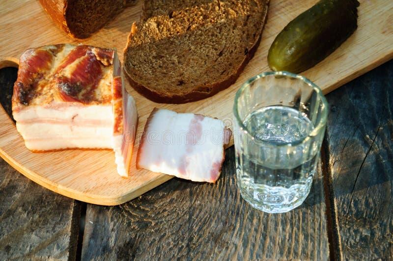 Ett exponeringsglas av vodka, bacon, bröd och gurkan fotografering för bildbyråer