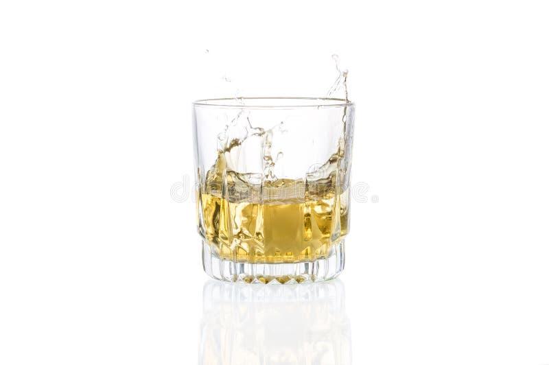 Ett exponeringsglas av whisky och stupat in i det iskub fotografering för bildbyråer