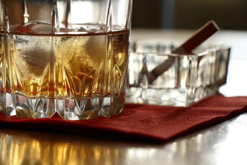 Ett exponeringsglas av whisky på vaggar och en röka cigarett royaltyfria bilder