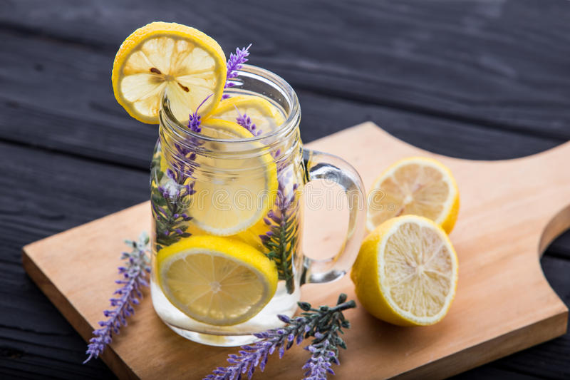 Ett exponeringsglas ingav vatten av citronen och lavendel arkivbild