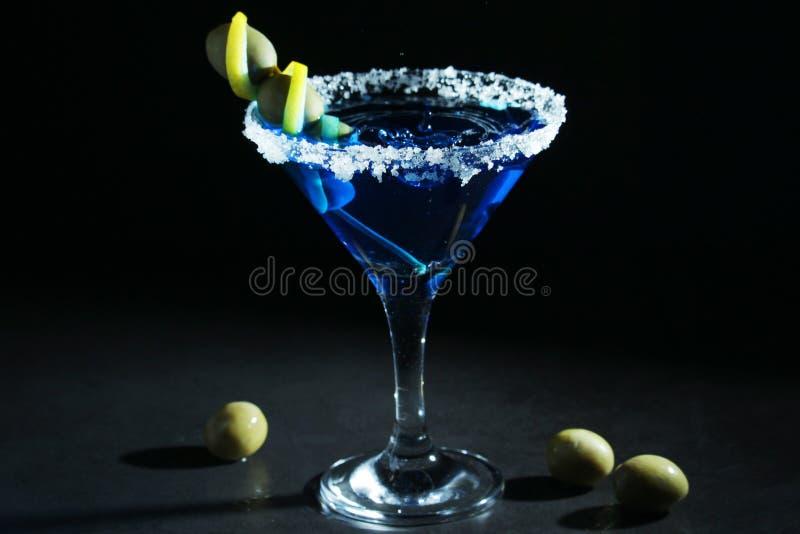 Ett exponeringsglas med den blåa martini coctailen royaltyfri bild
