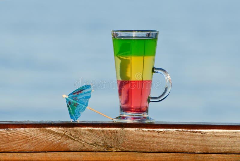 Ett exponeringsglas med detfärgade coctailar och coctailparaplyet mot havet royaltyfria bilder