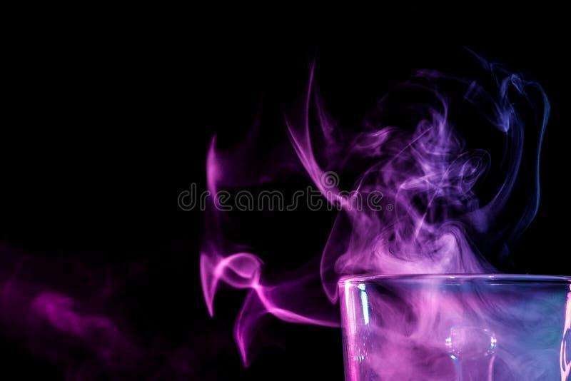 Ett exponeringsglas med färgrik rök arkivfoton