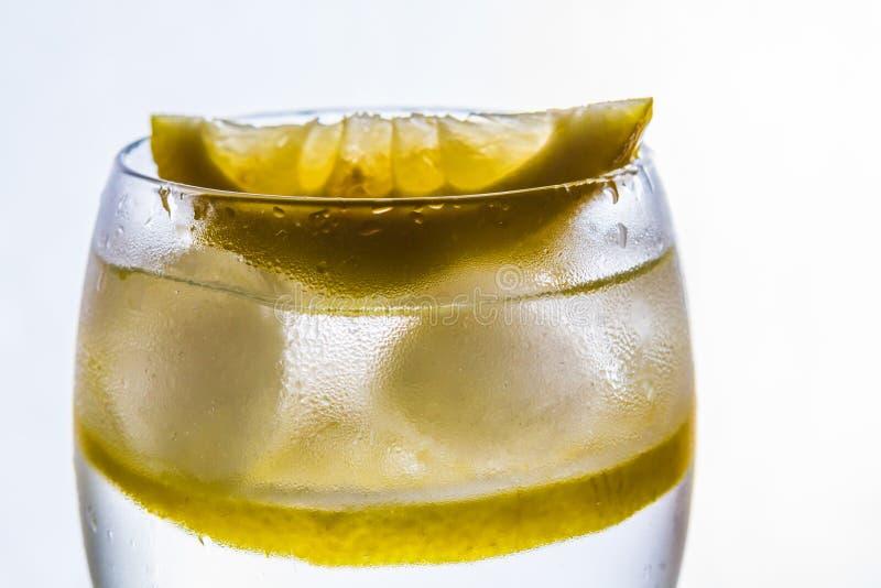 Ett exponeringsglas med vatten, is och citronen arkivbilder