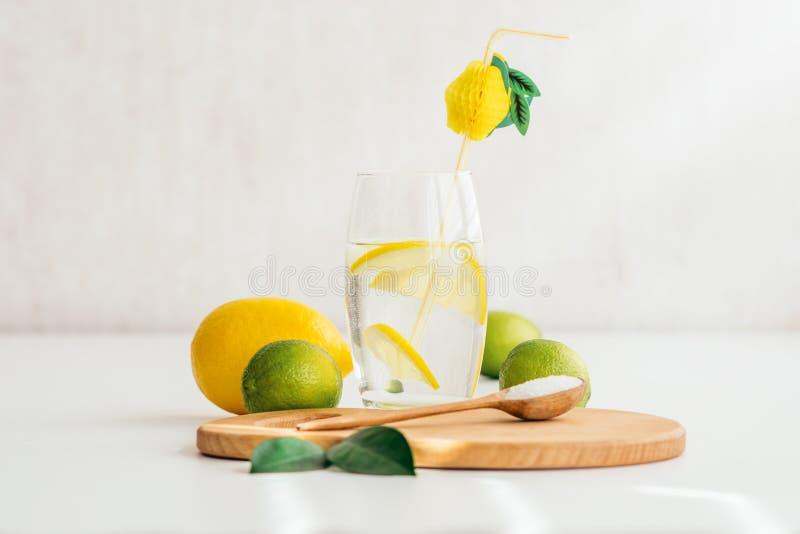 Ett exponeringsglas med vatten och citronen, en träsked med saltar på ett träbräde royaltyfri fotografi