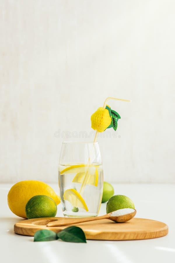 Ett exponeringsglas med vatten och citronen, en träsked med saltar på ett träbräde arkivfoto