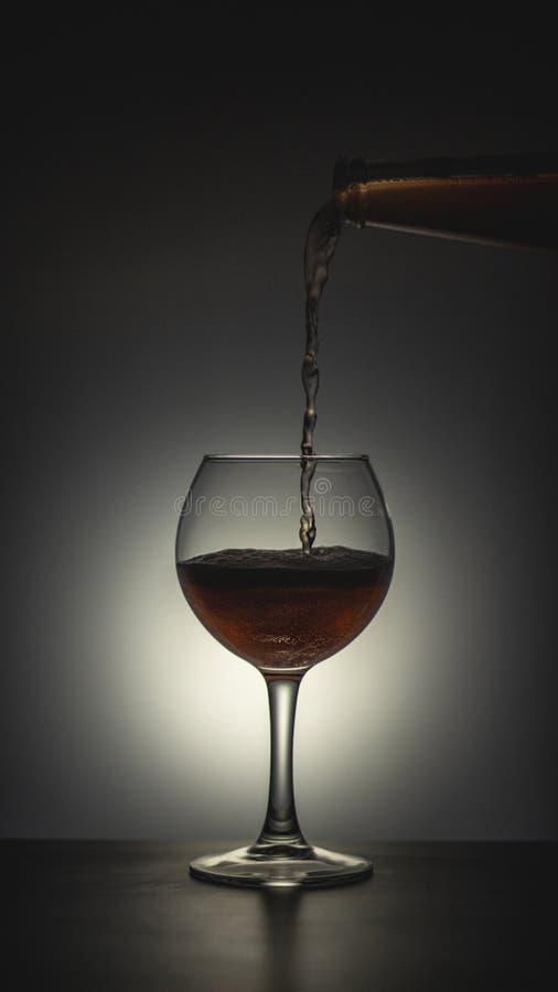 Ett exponeringsglas som hällde alkohol på en mörk bakgrund arkivbild