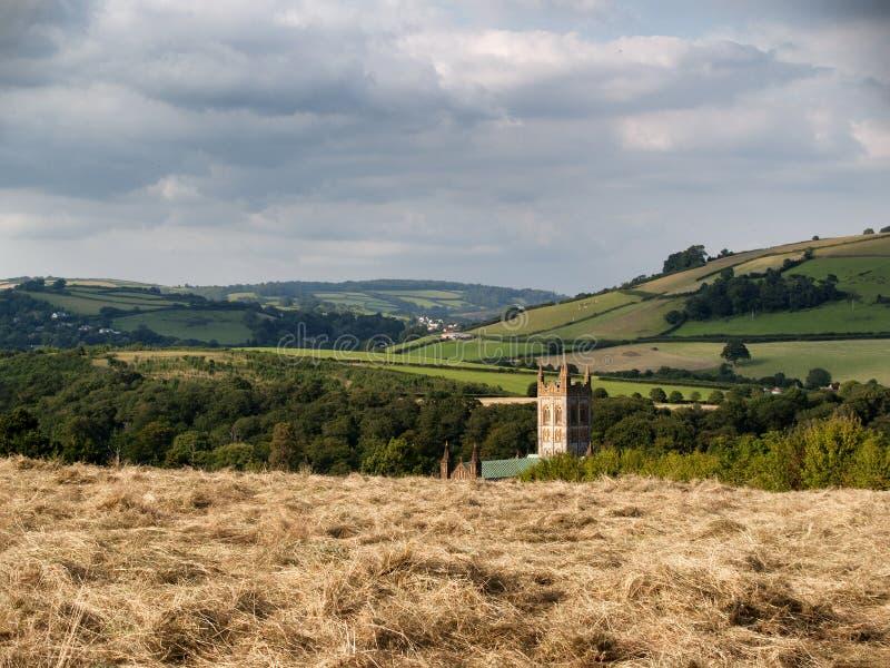 Ett fält av mejat hö med kyrkatornspiran som stiger i bakgrunden royaltyfri foto