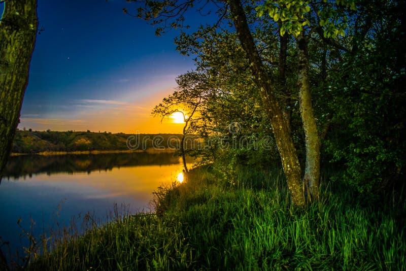 Ett färgrikt landskap, en stor måne, en soluppgång på en flod under ett träd, en tyst sommar, en vårdag Maj färger av naturen royaltyfria bilder