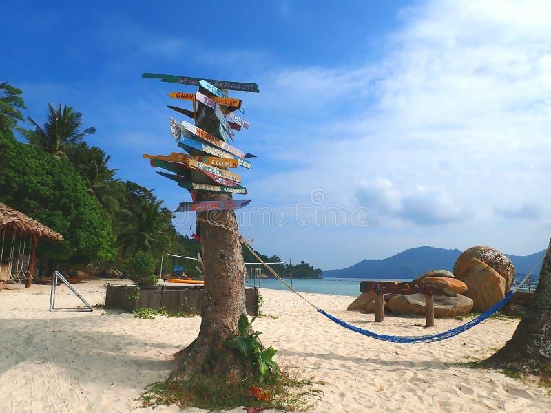 Ett färgrikt och attraktivt av loppdestination i kilometer som visas på trädet med en hängmatta som hänger på kokospalmen royaltyfria foton