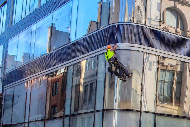 Ett fönster för manlokalvårdspegel på en hög löneförhöjningbyggnad Klättrare på jobb som yrkesmässigt fönsterrengöringsmedel arkivfoto