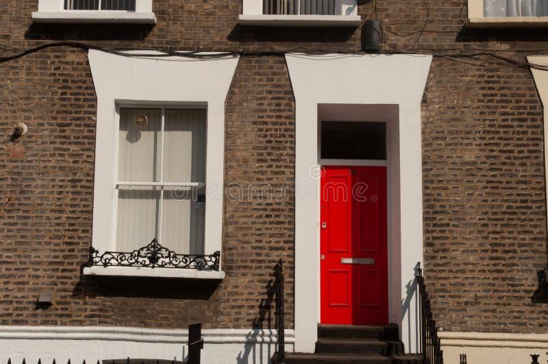 Ett fönster och en röd dörr med olik design i en tegelstenvägg London arkivfoton