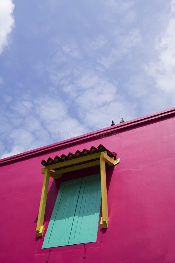 Ett fönster på en rosa vägg arkivbild