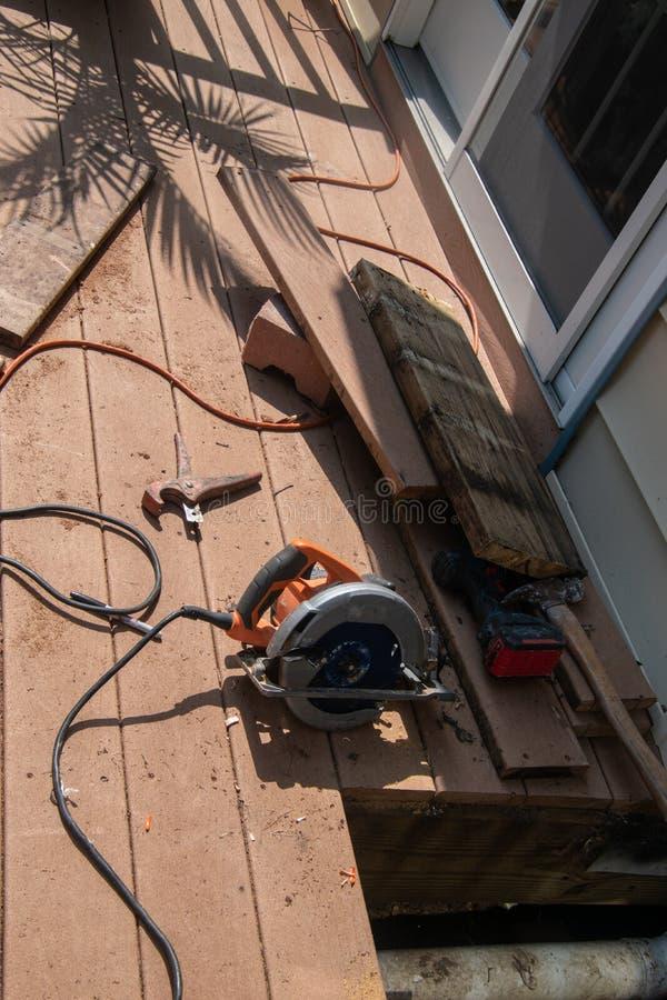 Ett fönstersnitt in i brunt trädäck för att att reparera ett dräneringproblem under däcket Det finns olika makthjälpmedel på royaltyfri fotografi