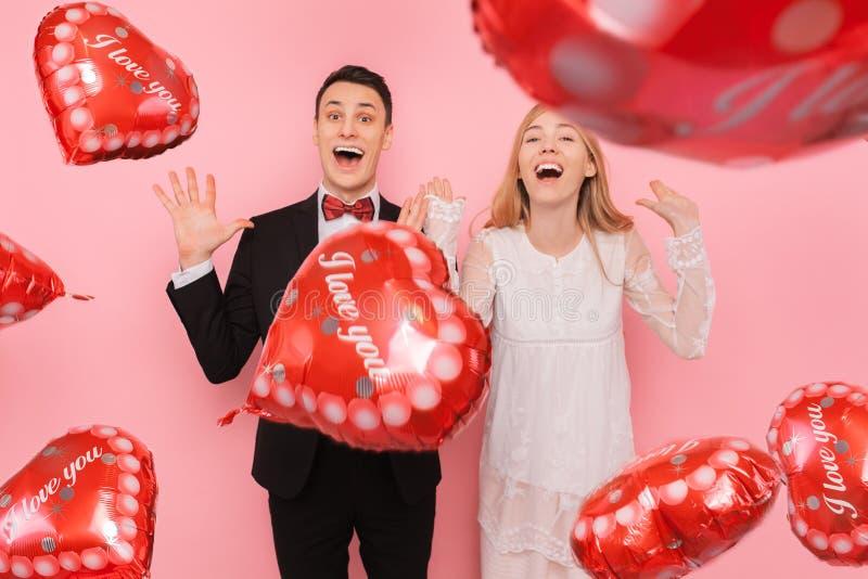 Ett förälskat par, en man och en kvinna som rymmer ballonger i formen av en hjärta på en rosa bakgrund, tycker om valentins dag royaltyfria foton