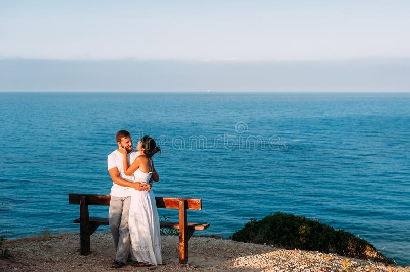 Ett förälskat par möter gryningen på havet royaltyfri bild
