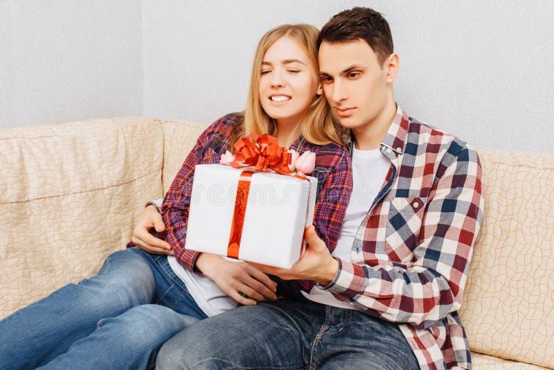 Ett förälskat ungt par, en man gratulerar en kvinna, genom att ge henne en bukett av tulpan och en gåva som hemma sitter på soffa royaltyfri fotografi