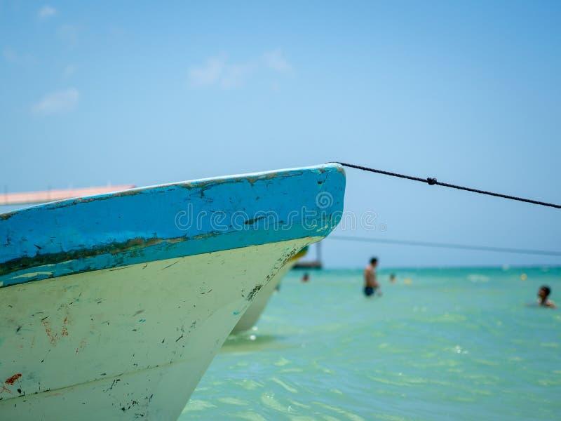 Ett förtöjt fartyg i klart blått vatten med folk som simmar i bakgrunden royaltyfria bilder