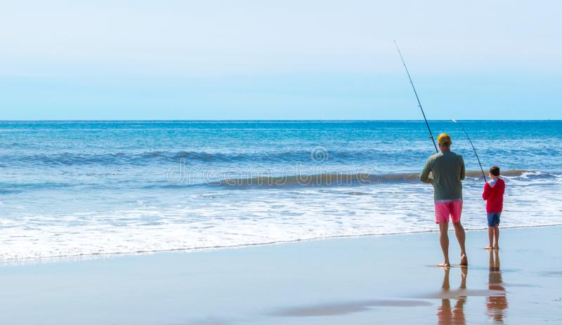 Ett fader- och sonfiske på stranden arkivfoto