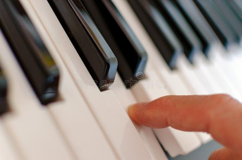 Ett finger trycker på en tangent på ett piano arkivbild