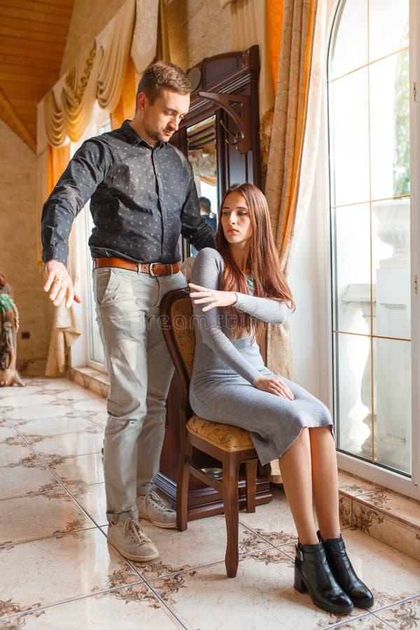 Ett flickasammanträde på en stol skjuter en hand för grabb` s arkivbild