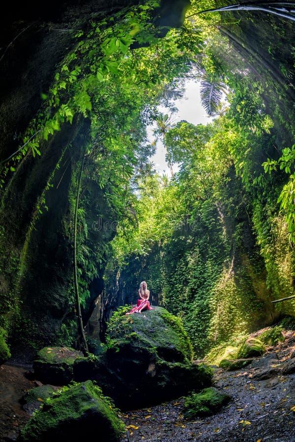 Ett flickasammanträde på en vagga på den Tukad Cepung vattenfallet i bali 3 arkivfoton