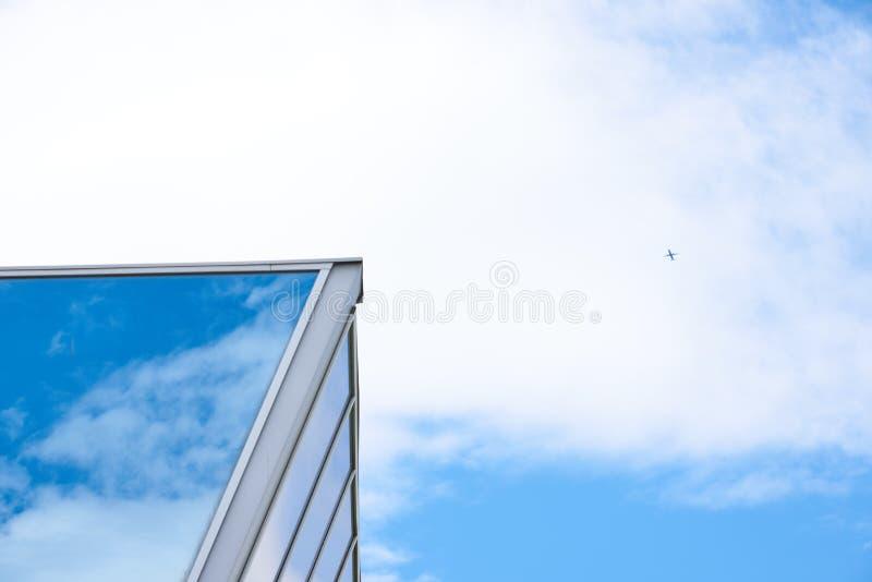 Ett flygplan, en himmel, en byggnad och en himmel som reflekterar på en byggnad royaltyfri bild