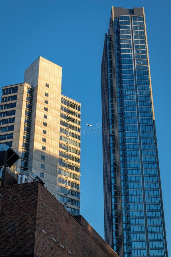 Ett flygplan passerar mellan två högväxta New York City skyskrapor på en eftermiddag för sen sommar arkivbild