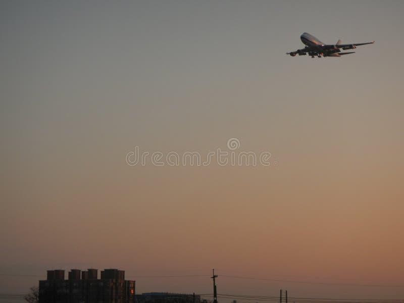 Ett flygplanflyg över bostads- byggnad royaltyfria bilder