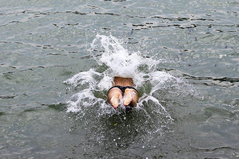 Ett folk hoppade in i vattnet, fot ben och höfter som plaskar royaltyfri foto
