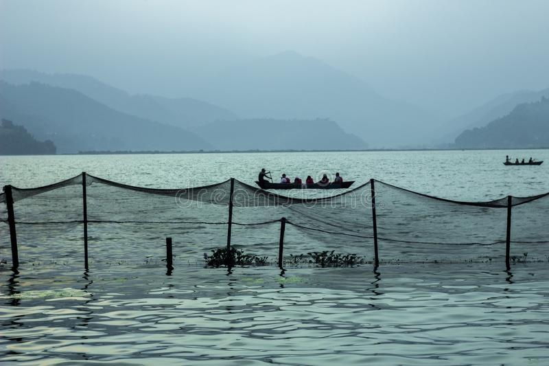 Ett folk i ett fartyg på sjön mot aftonkonturerna av berg fisknät på vattnet royaltyfri fotografi