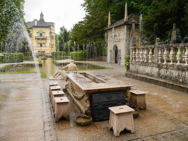 Ett forntida stenar tabellen med trickspringbrunnen på den Hellbrunn slotten royaltyfri foto