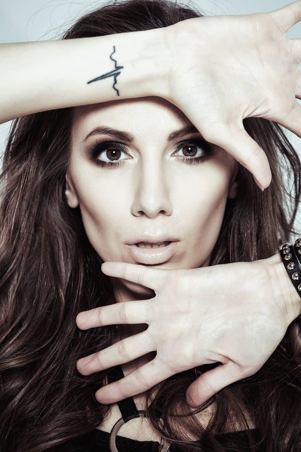 Ett foto av den härliga kvinnan är i modestil, Esquirestil, glamur Flicka med en tatuering på hennes handled royaltyfri fotografi
