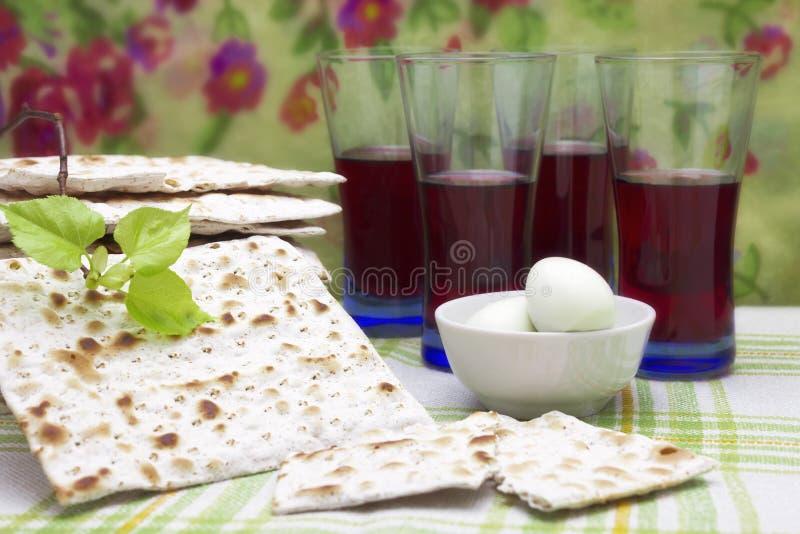 Ett foto av judiskt Matzahbröd, kokta ägg, koschert rött vin och en lindträdfilial Matzah för de judiska påskhögtidferierna Se royaltyfria bilder