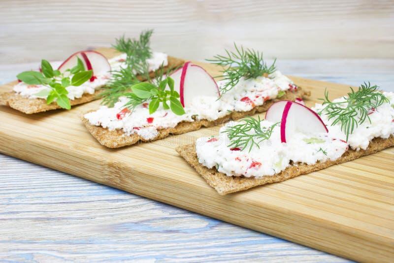 Ett foto av smällare, knaprigt rostat bröd för rågbröd med keso som dekoreras med rädisan, gurkan, dill och basilika, lämnar träb arkivbilder