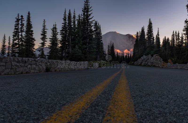 Ett foto för låg vinkel av vägen som upp till leder Mount Rainier på solnedgången, Washington, USA arkivbild