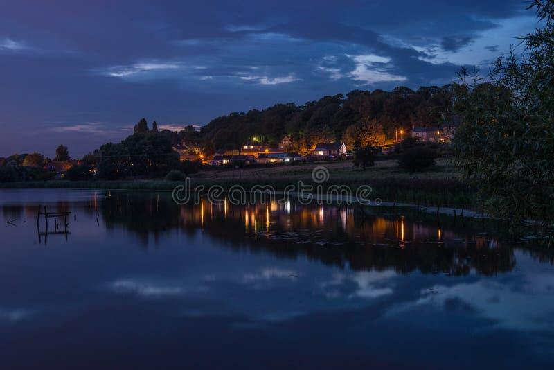 Ett foto för sen afton av en by reflekterad i vatten arkivbild