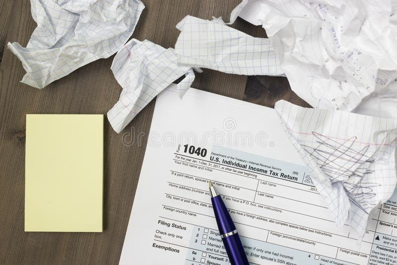 Ett foto från ovannämnt av den USA IRS skattformen 1040, gulinganmärkningar, skrynklade pappers- ark och en penna på trätabellen  royaltyfria bilder