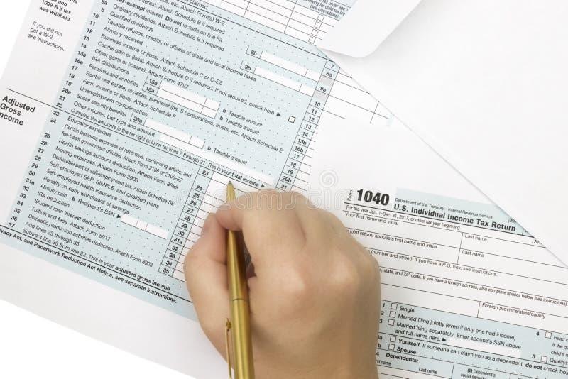 Ett foto från ovannämnt av en skattform 1040 En kvinna som undertecknar eller fyller formen Inkomstskattformen 1040 Bästa veiw, s arkivbilder